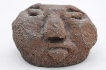 Brutalist iron head candle holder, naive art ugly face old man in the moon?