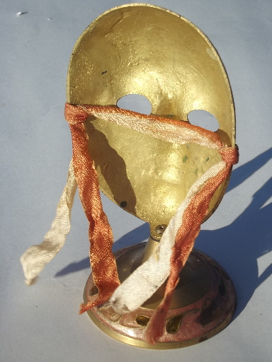 Enameled brass mask on display stand, masked face made in India